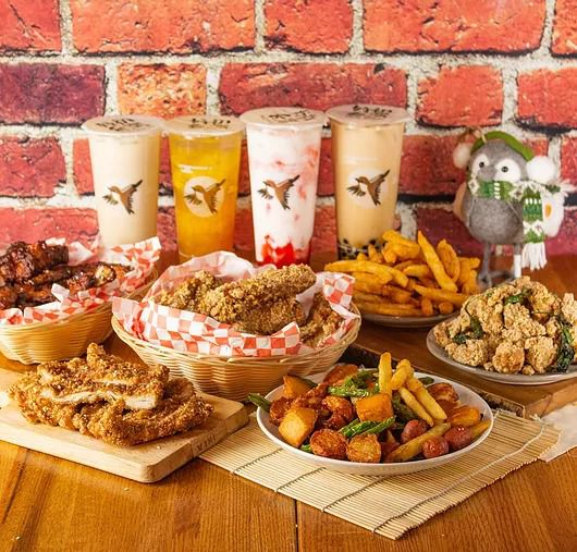 A variety of fried chicken, sides, and bubble teas spread out on a table.
