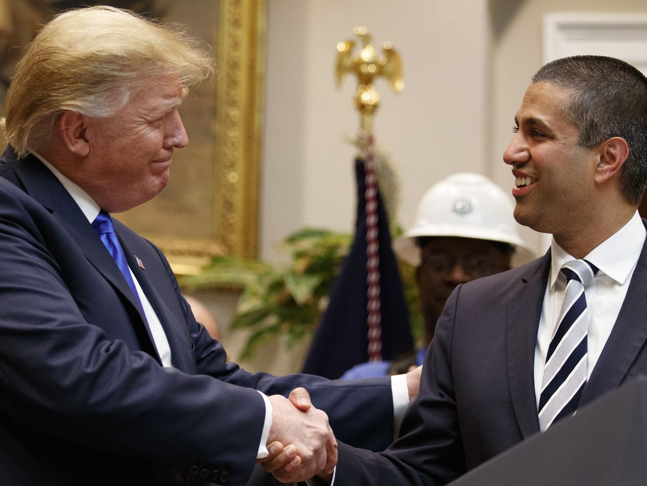 President Donald Trump and FCC Chair Ajot Pai shake hands.
