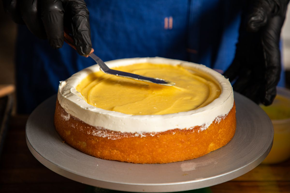 The bottom layer of a cake is topped with yellow icing