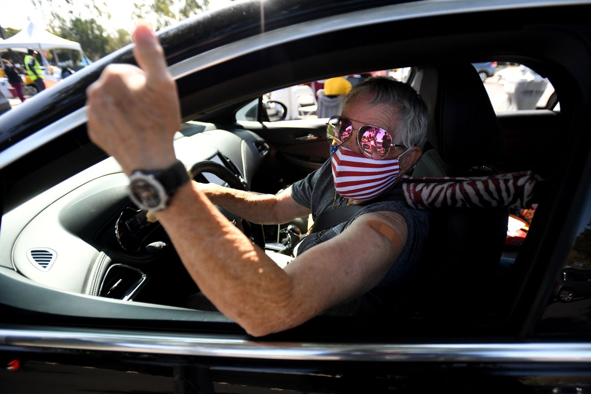 A woman with short gray hair, reflective sunglasses, and a US flag mask leans out of her car window to give a thumbs-up. A band-aid is visible on her upper arm.