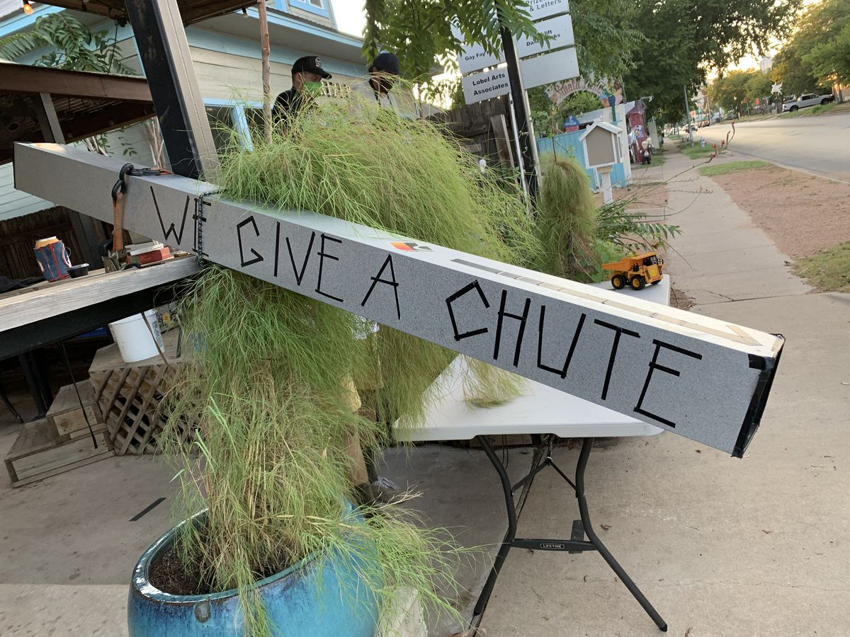 """A light gray metal chute with the phrase """"We Give A Chute"""" written on it with black tape, placed at an angle from an elevated table onto a lower folding table amid planted greenery outside"""