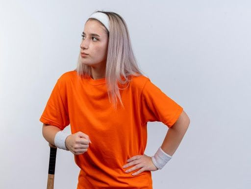 Confident, young caucasian girl with braces wearing headband and wristbands put arm around baseball bat