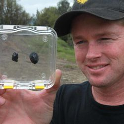 """Robert Ward displays two pieces of a meteorite he found at a park in Lotus, Calif., Wednesday, April 25, 2012.  Ward found the pieces from a meteor that was probably about the size of a minivan  when it entered the Earth's  atmosphere with a loud boom about 8 a.m. Sunday.  The rocks came from a meteor, believed to between 4 to 5 billion years old.  Ward, who has been hunting and collecting meteorites for more than 20 years,  said they are believed to be """"one of the oldest things known to man and one of the rarest types of meteorites there is."""