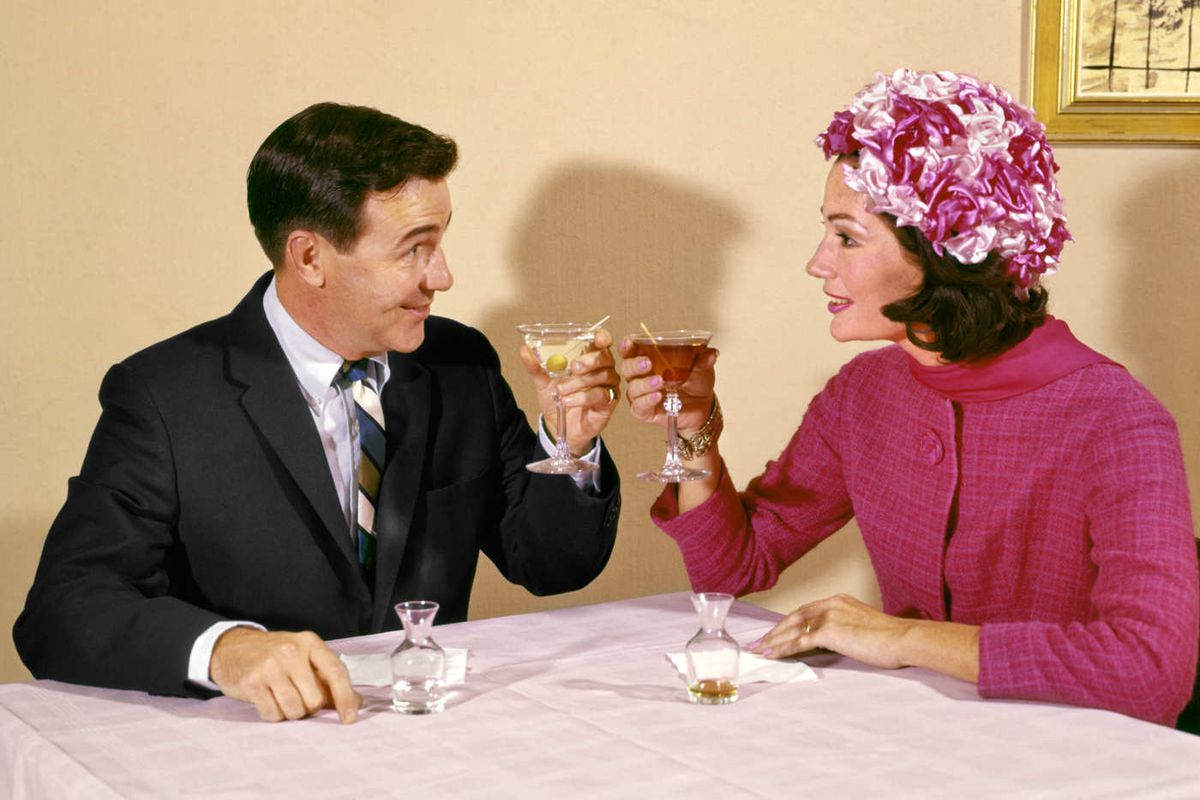 A man and a woman clink martini glasses