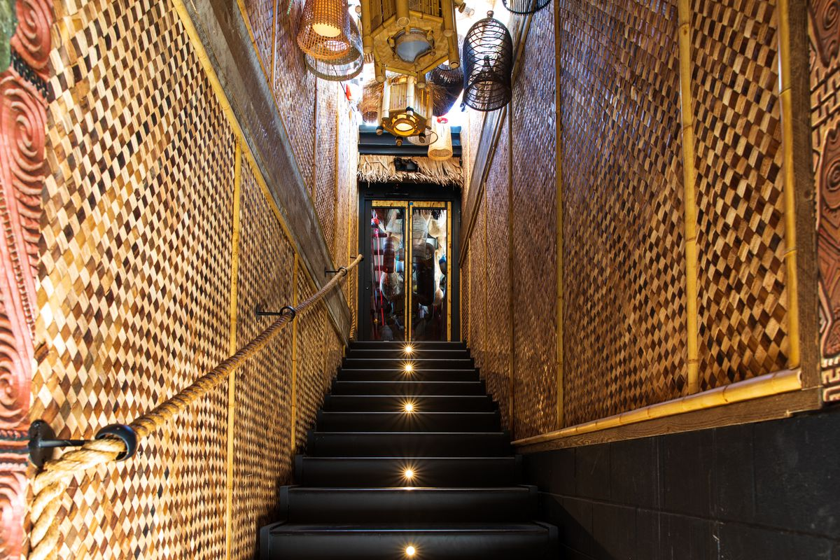 A staircase leads up flanked with woven basket walls and hanging baskets from the ceiling.