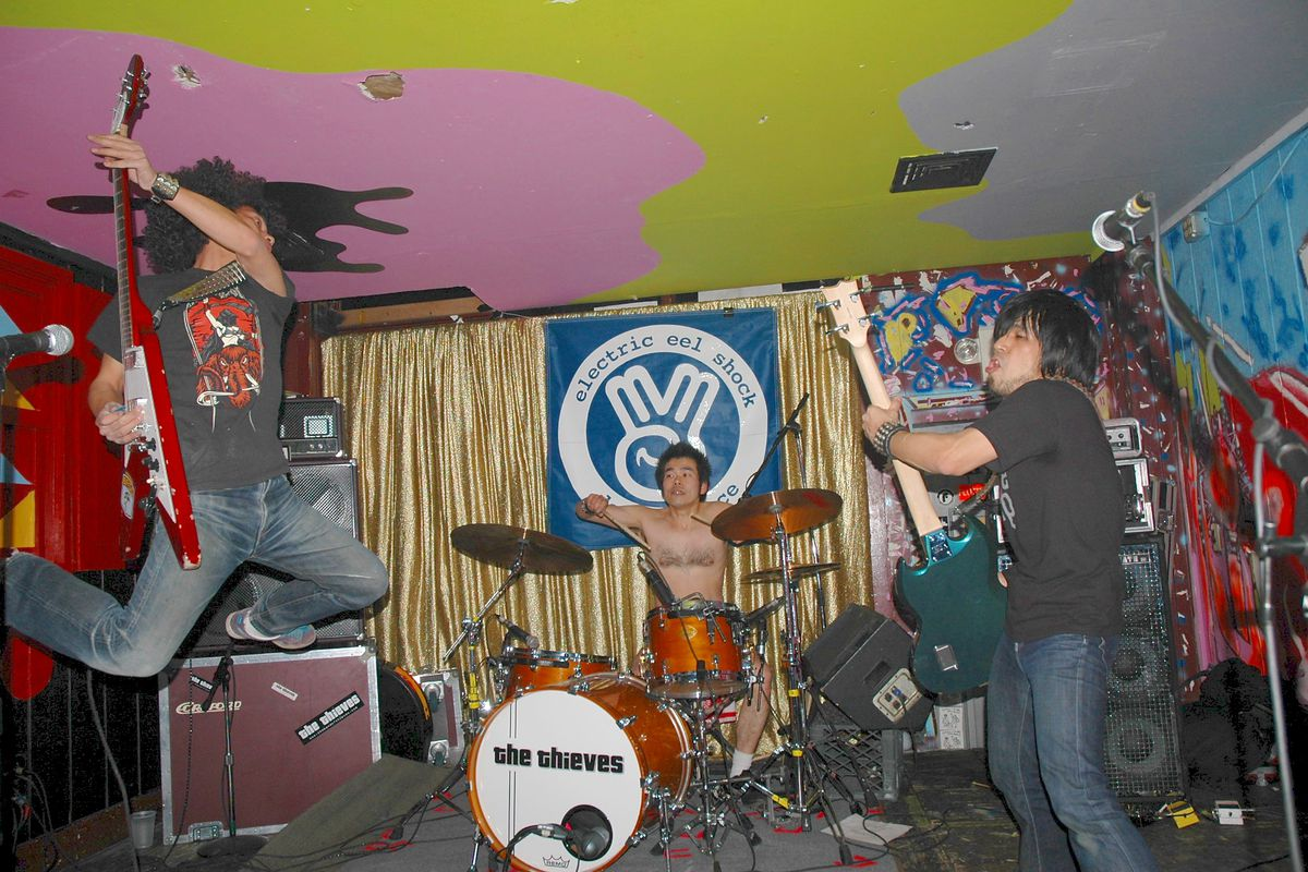 band playing small room with colorful ceiling