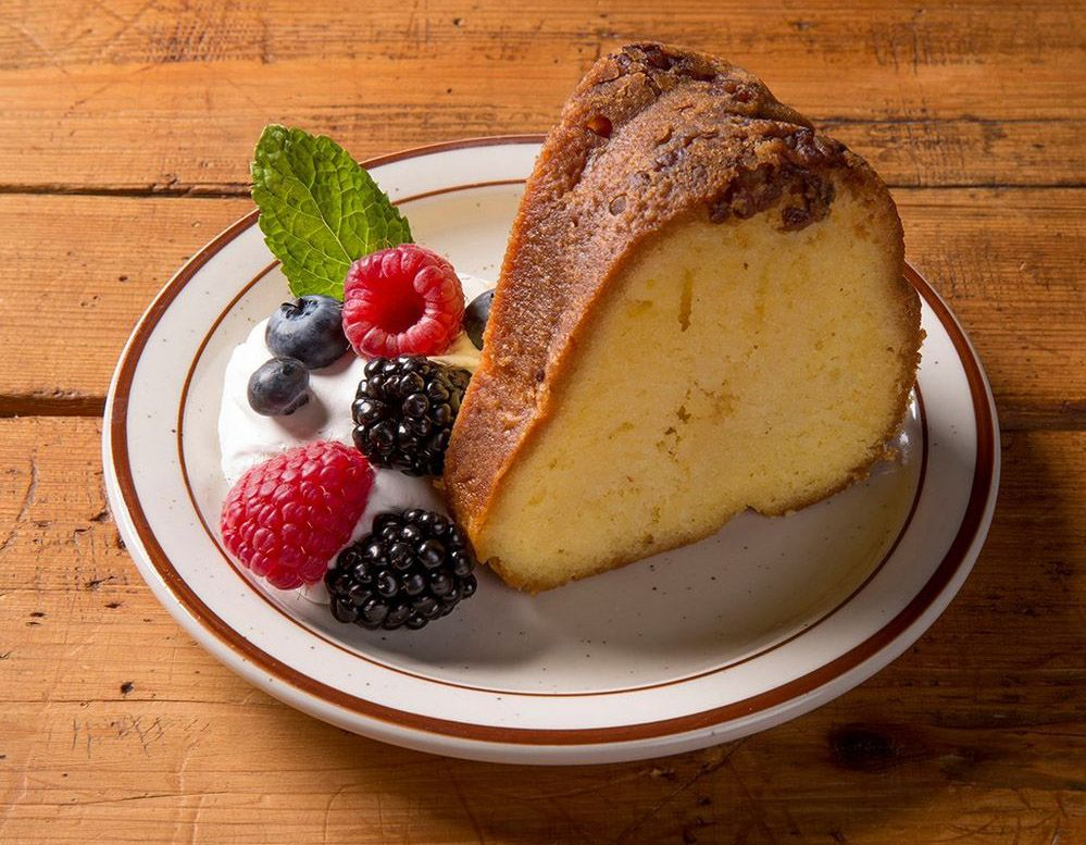 A slice of bundt-style rum cake on a plate with fresh whipped cream and berries.