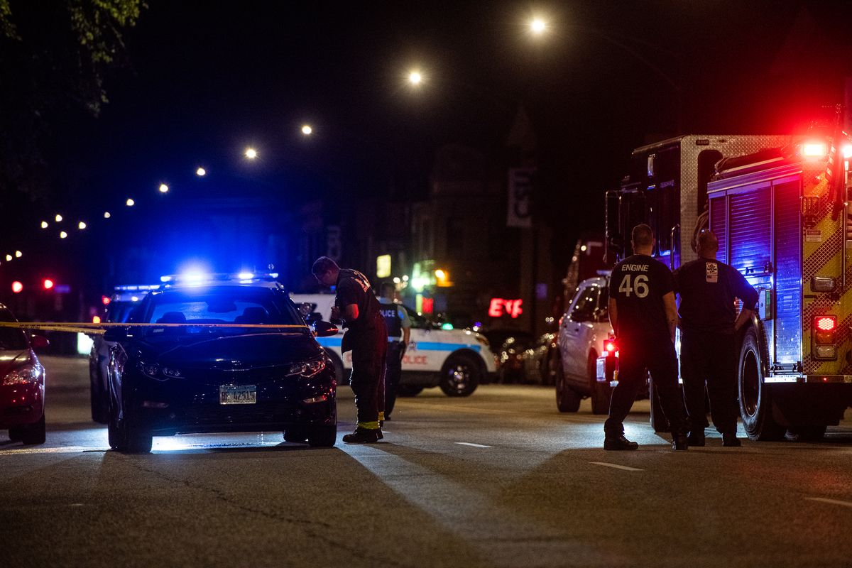 A Chicago Fire Fighter looks at a shot up vehicle which was involved in a shoot out with an off-duty police officer Aug. 24.