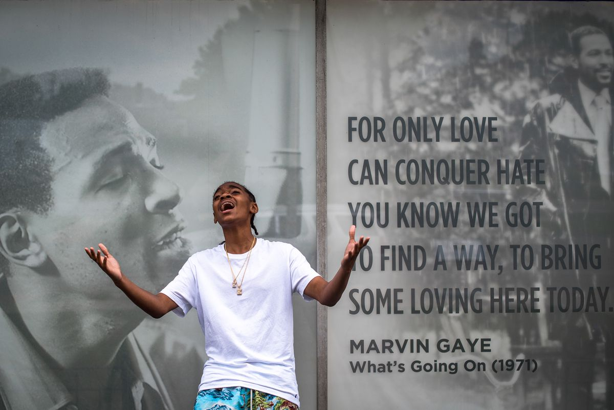 """Teenager King Bethel sings in front of a mural of Marvin Gaye, with lyrics from the song """"What's Going On"""" that read, """"For only love can conquer hate. You know we got to find a way, to bring some loving here today."""""""