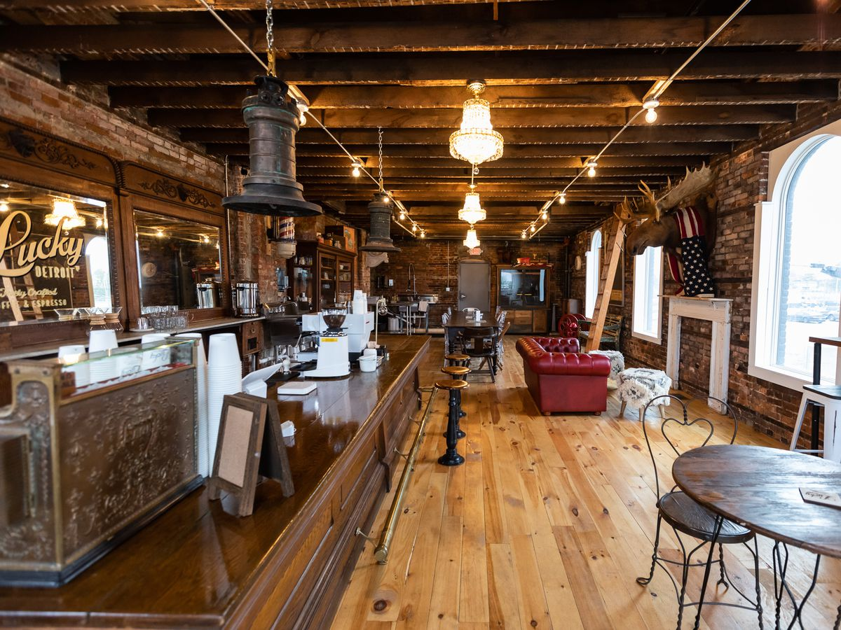A coffee shop with a bar area with vintage stools and lots of wood that makes it look like a saloon.