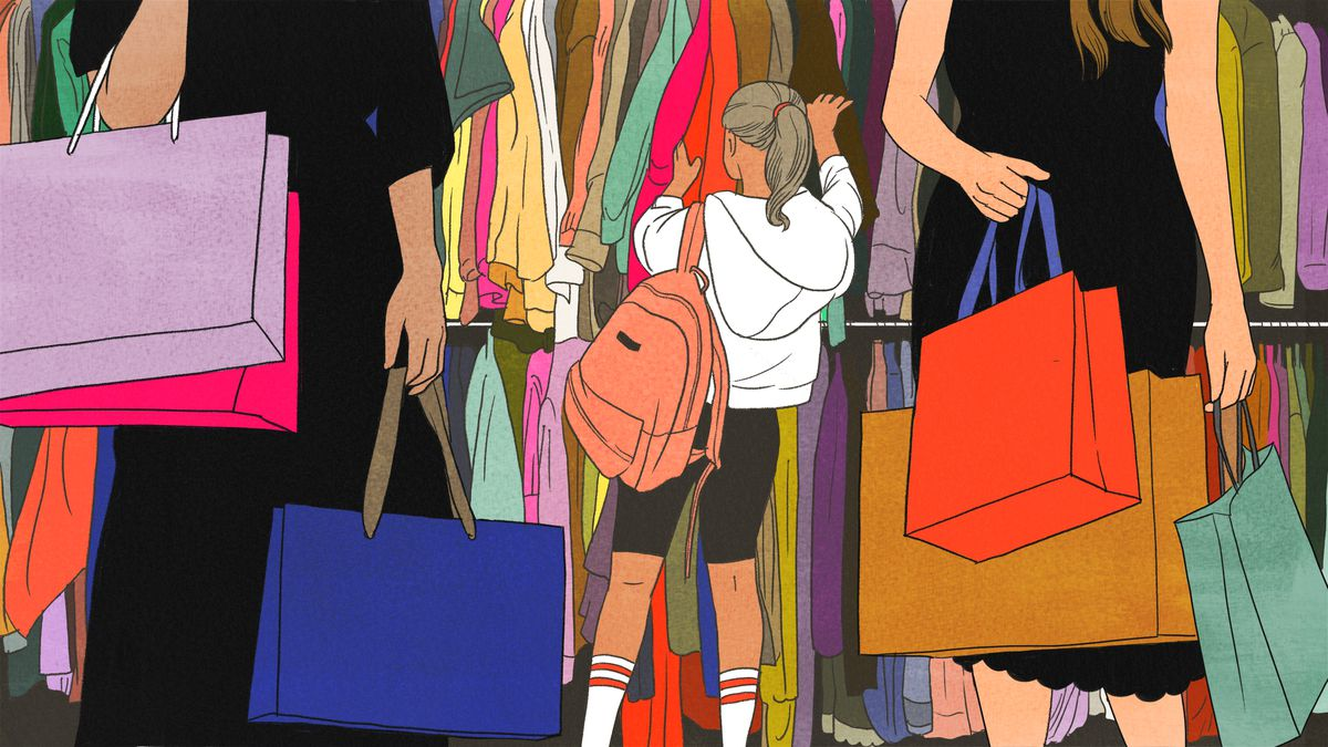Young girl looks through a wall of clothing surrounded by other shoppers.