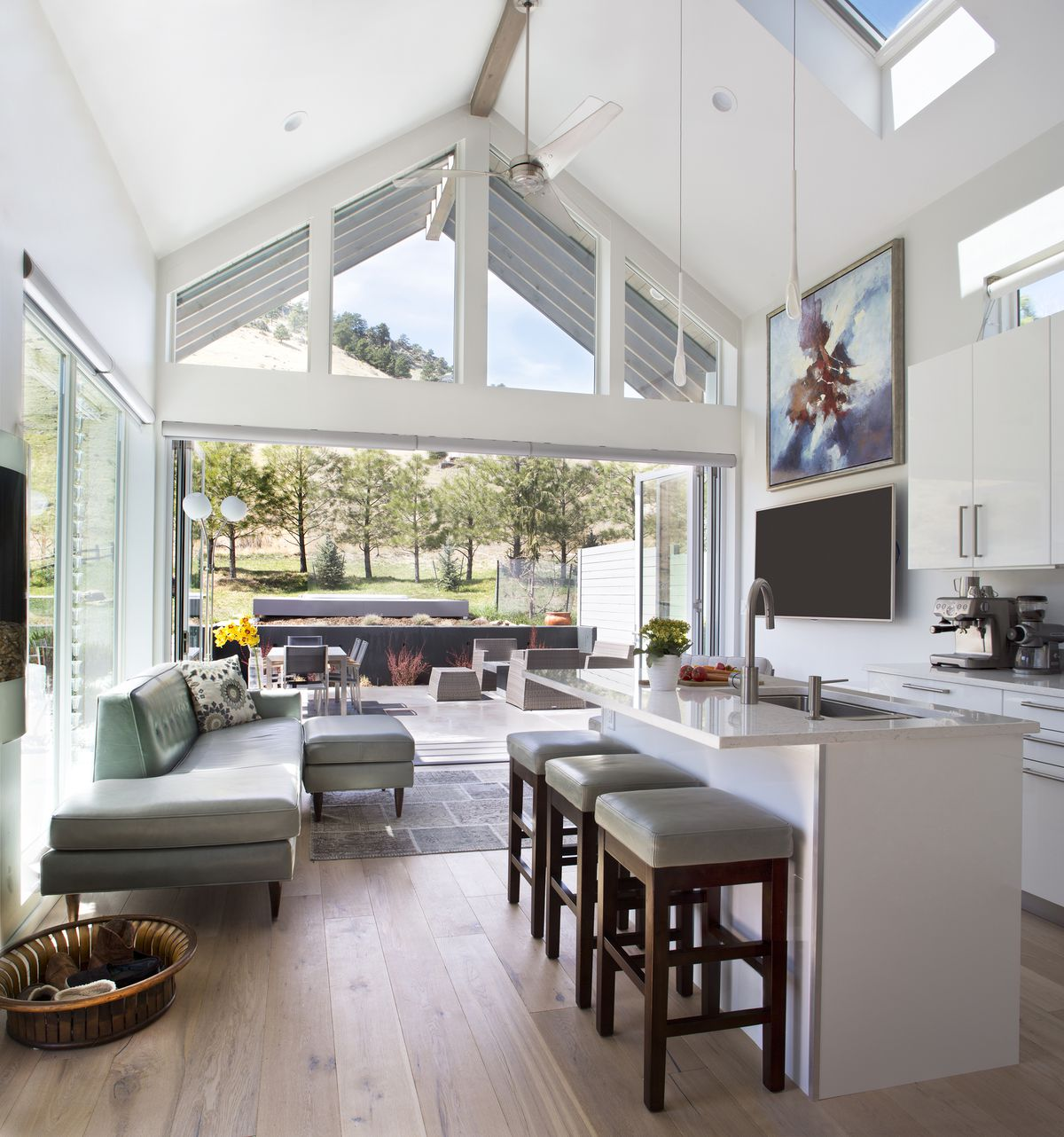 Looking out from the kitchen, you see very high ceilings, glass doors that open a wall of the house, and lots of windows.
