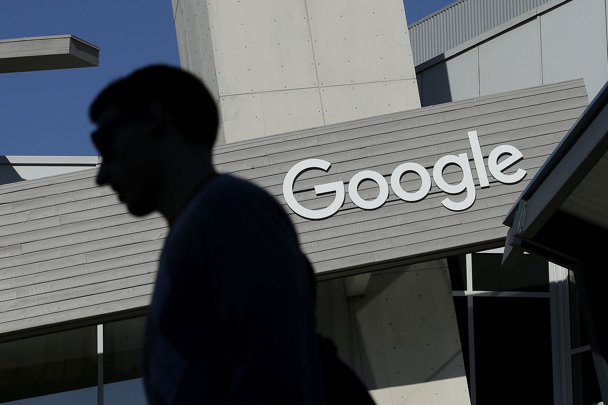 FILE - In this Nov. 12, 2015, file photo, a man walks past a building on the Google campus in Mountain View, Calif. Voters in a Northern California city will decide whether Google and other tech companies should help pay for the traffic headaches and othe