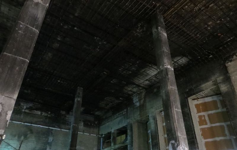 A dark, windowless space with raw concrete columns and walls. The ceiling is scorched black from a previous fire.