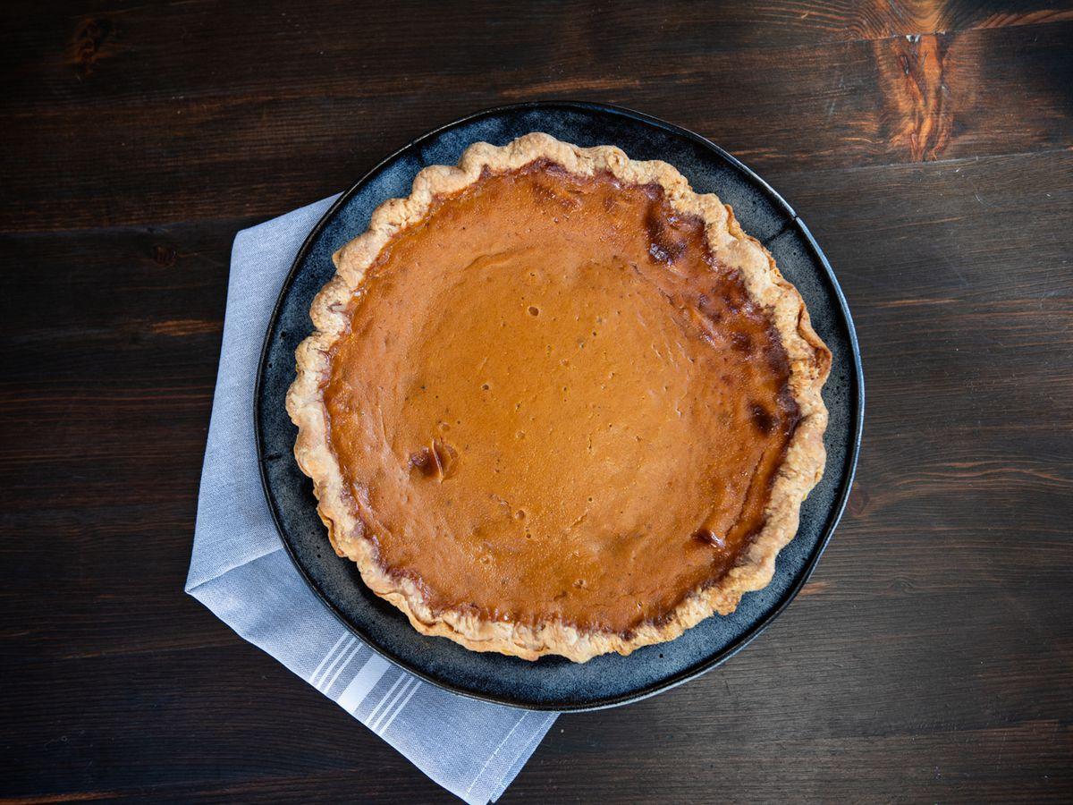 A top-down view of a pumpkin pie against a dark wood table.