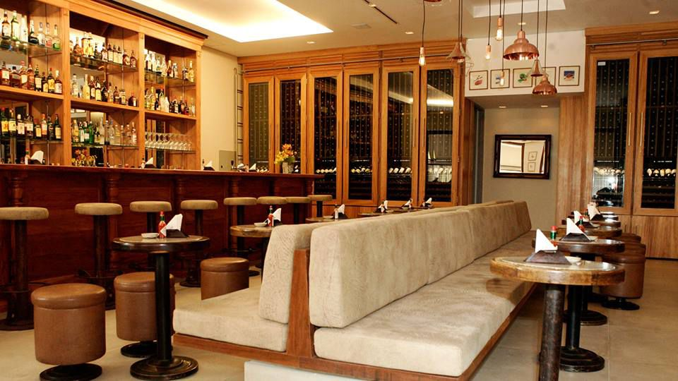 A dining room and bar with long back-to-back  banquets running the length of the room, small bar tables, and a well-stocked bar off to one side.