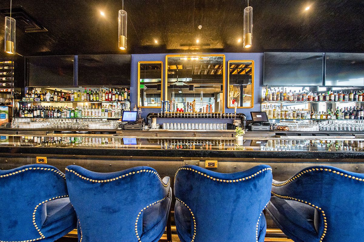 The bar at Pistol Whip is lined with liquor and wine with plush blue stools to sit on.