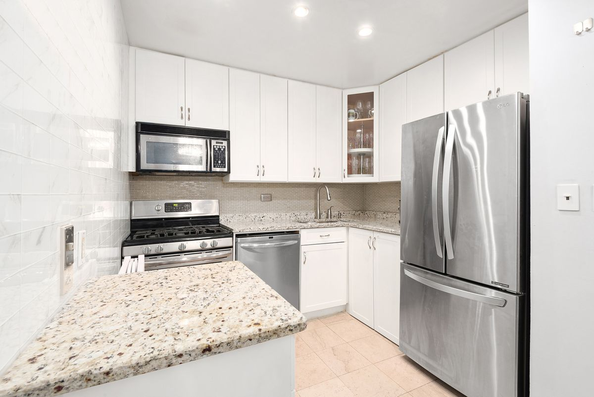 A kitchen with marble counters and white cabinetry.