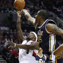 Utah Jazz's Derrick Favors (15) defends Portland Trail Blazers' Jonny Flynn (3) during the second quarter during of NBA basketball game Wednesday, April 18, 2012, in Portland, Ore.  (AP Photo/Rick Bowmer)