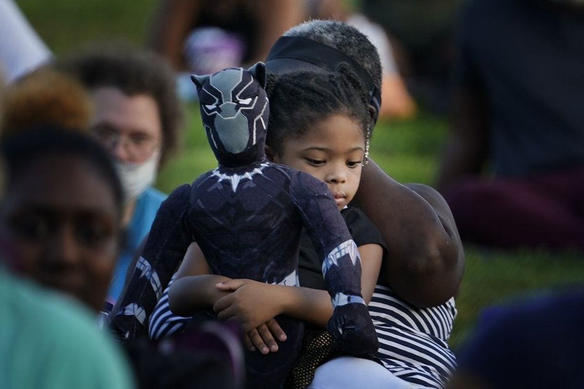 Girl holding Black Panther doll