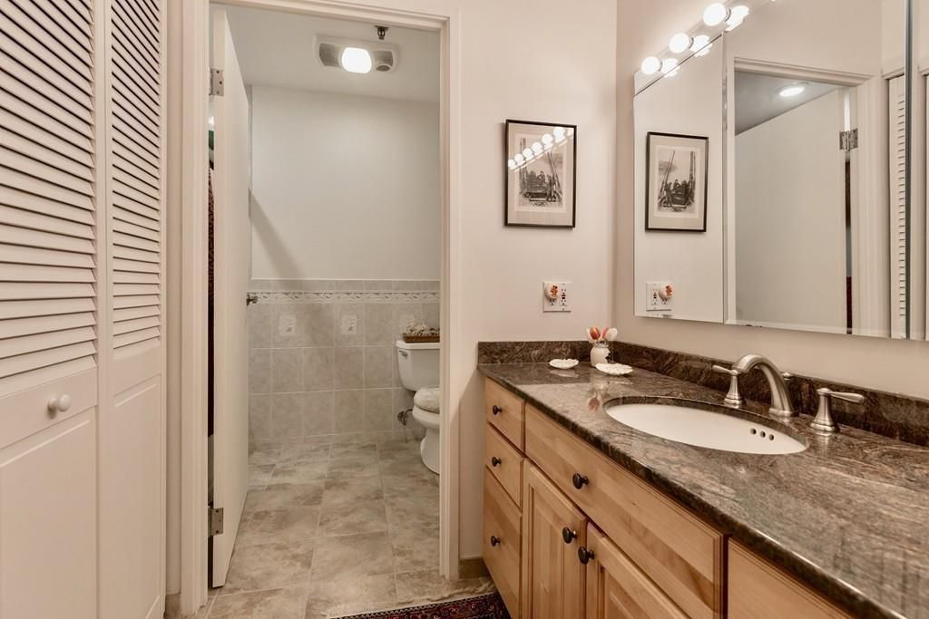 A bathroom with a long counter and the toilet in a cubby hole at the end.