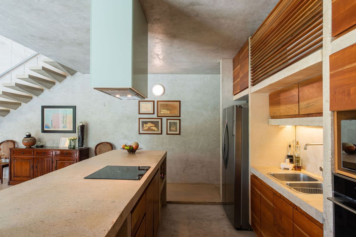 An open kitchen has an island on one side, and appliances with wooden cabinetry on the other.