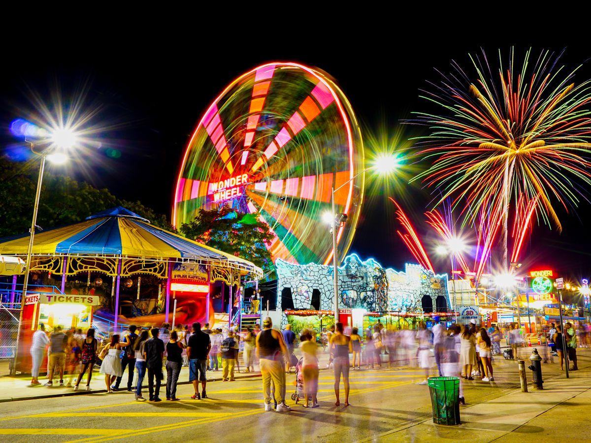 An amusement park with a carousel, Ferris wheel, and other rides, with fireworks going off overhead.