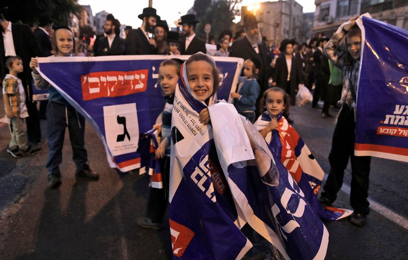 Israeli children wrap themselves in rally banners at a 2019 election rally.