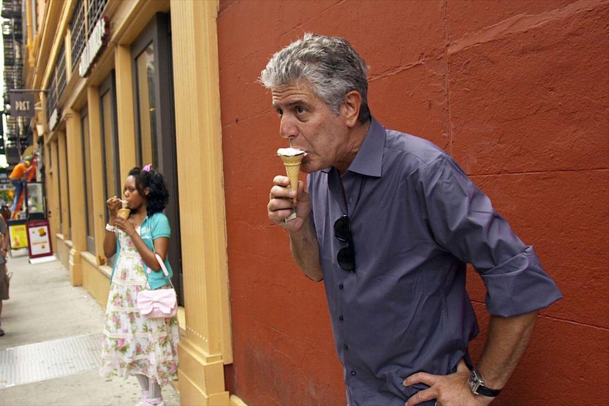 Anthony Bourdain eats an ice cream cone against an orange wall.