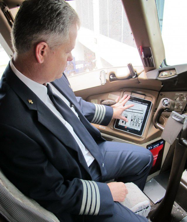An American Airlines pilot consults an Apple iPad in the cockpit.