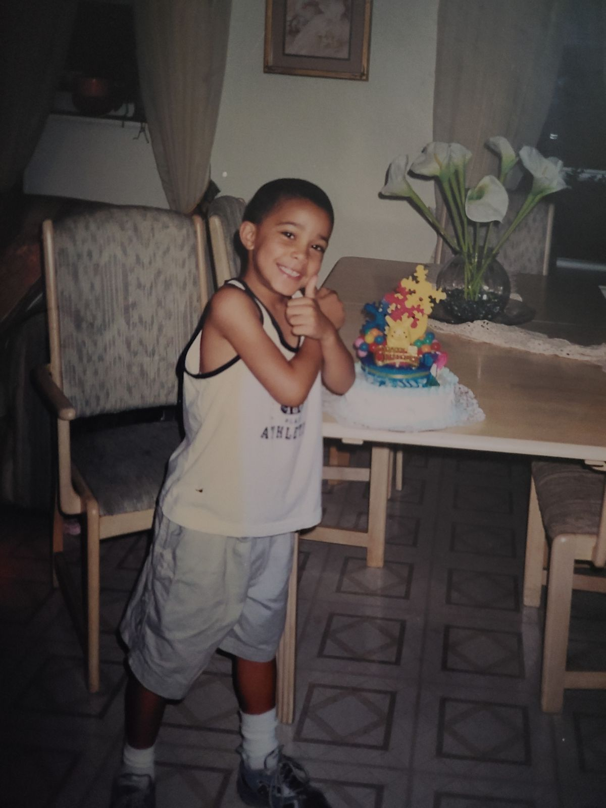 A boy smiles and gives a thumbs up toward the camera, standing at a dining room table next to a birthday cake.