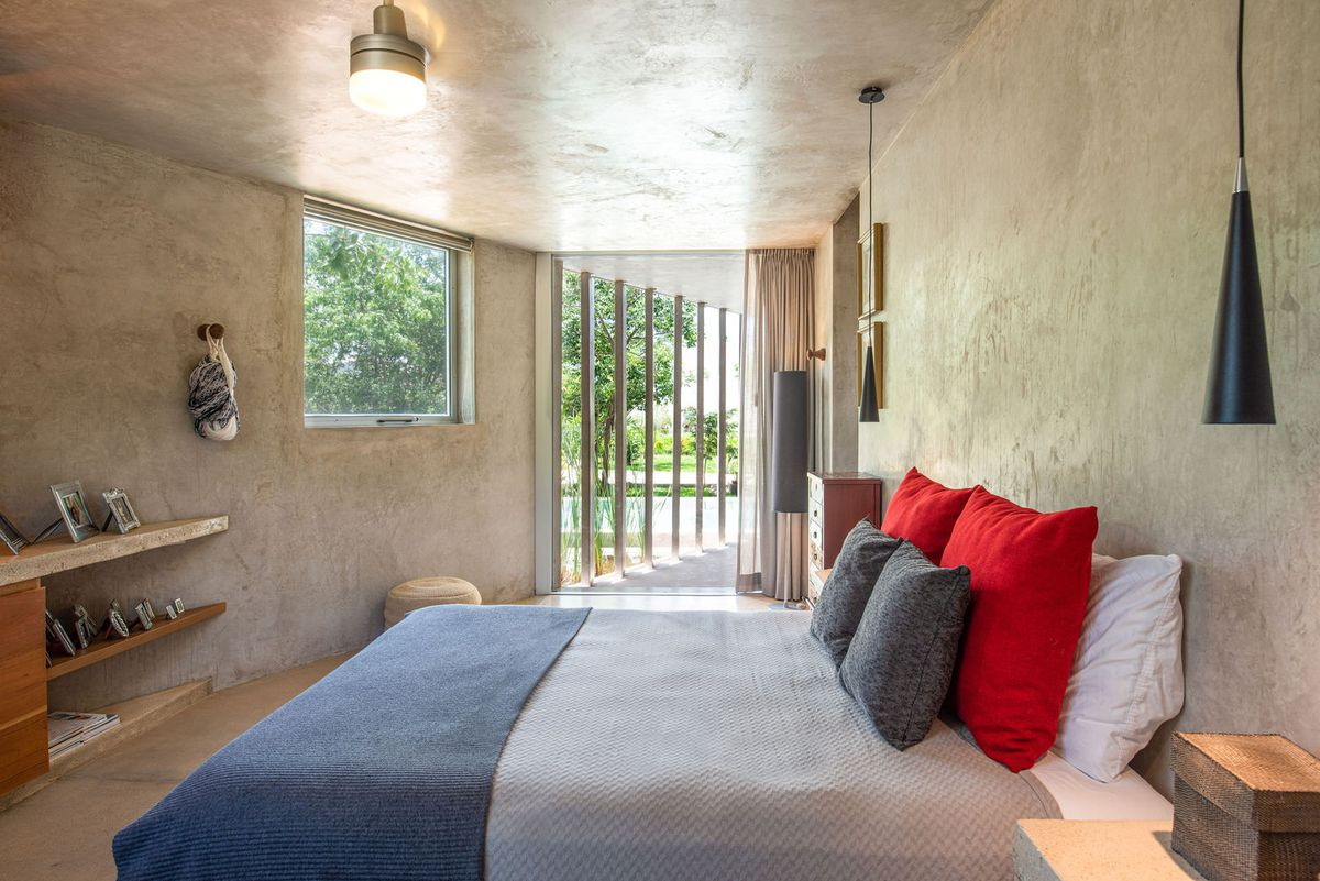 A bedroom with stucco concrete walls has views to the outside. A bed has bedding with blue, red, and gray colors.