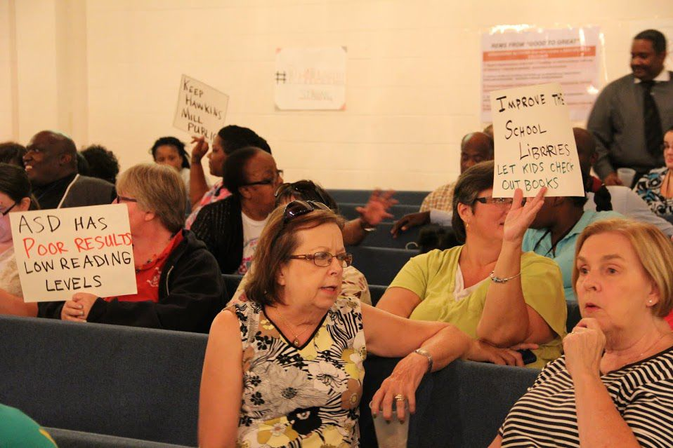 Attendees hold up signs in favor of keeping two Memphis schools in the Shelby County school district.