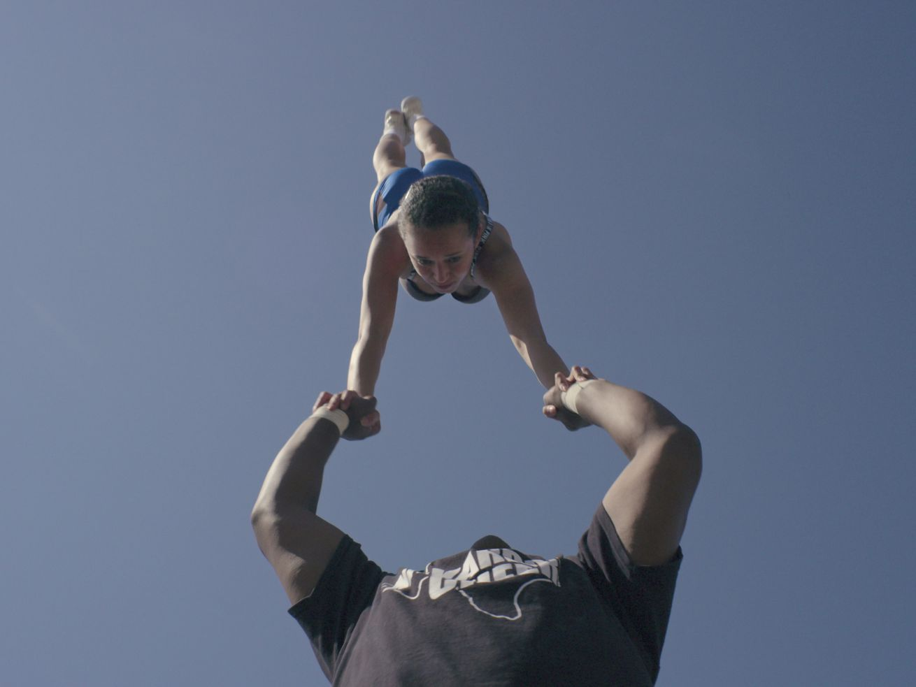A male cheerleader holds a young woman in a handstand over his head.