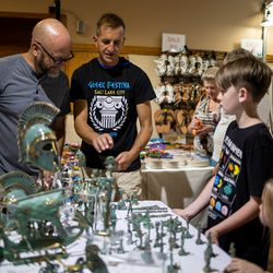 Alex Vasilatos, second from left, shows off bronze items made in Greece to Doug Littell, left, and his grandchildren, Aiden Smith, 10, and Emi Smith, 5, at the Greek Festival in Salt Lake City on Friday, Sept. 10, 2021.