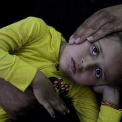 In this Monday, Sept. 10, 2012, photo, Syrian Mohammed Ramadan, 46, whose displaced from his home in Dir el Zour, due to fighting between the rebels and government forces, comforts his daughter Haneen, 5, who suffers from a lung infection, while waiting to be examined by a  doctor at a makeshift hospital in Suran, on the outskirts of Aleppo, Syria. The days are still hot across the fertile plains of northern Syria, but at night there is a hint of a chill an ominous harbinger of winter's approach and the deepening of the humanitarian crisis gripping a country wracked by civil war.