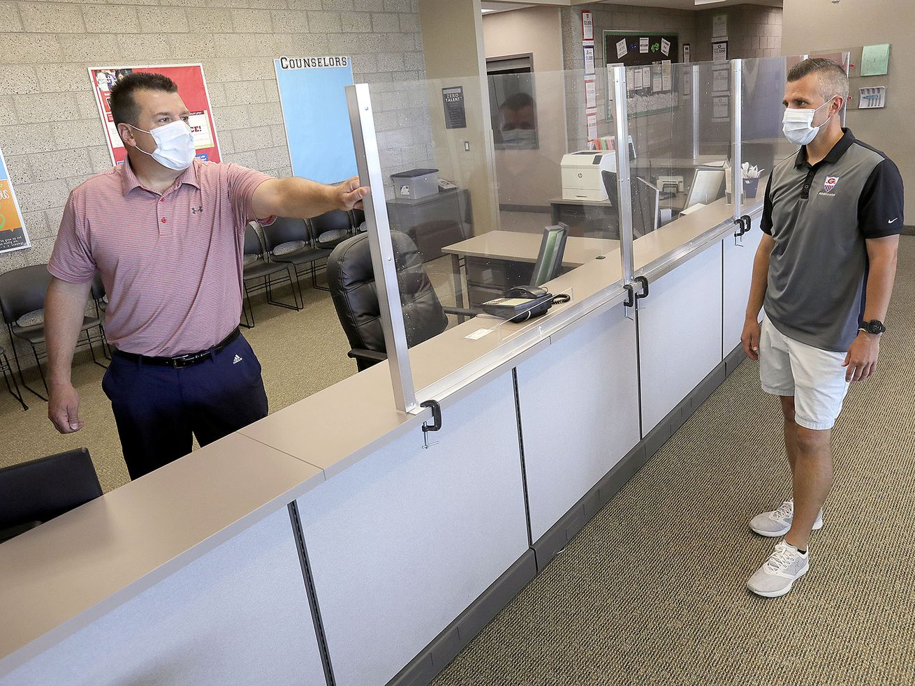 Granger High School Principal David Dunn and assistant principal David Beck show plexiglass walls that were recently installed at the West Valley school on Thursday, July 9, 2020. The plexiglass was installed to help prevent the spread of COVID-19.