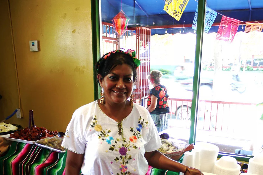 Chef Rocio Camacho stands inside her colorful Mexican restaurant, wearing a white shirt.