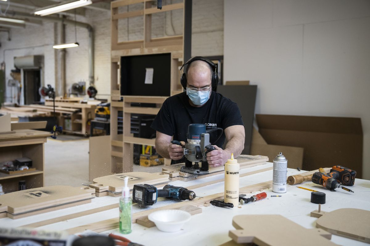 Jason Wade, lead carpenter at Pac Team, uses a template to cut plastic for face shields at the factory at 4447 W. Armitage Ave.