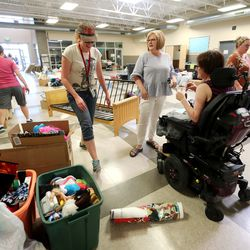 Vice Principal Rebecca Howland and Principal Diana Brantley talk with teacher Ravien Parsons as they organize yard sale items at Summit Academy in Bluffdale on Friday, June 19, 2020. Parsons has experienced a sudden disability after being diagnosed with stiff-person syndrome. The charter school where she teaches is holding the fundraiser to help her buy a wheelchair-accessible van so she can continue to work and more effectively live her life.