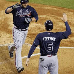 Atlanta Braves' Brian McCann greets Freddie Freeman (5) at the plate after hitting a two-run home run against the Arizona Diamondbacks during the fifth inning of a baseball game, Friday, April 20, 2012, in Phoenix.