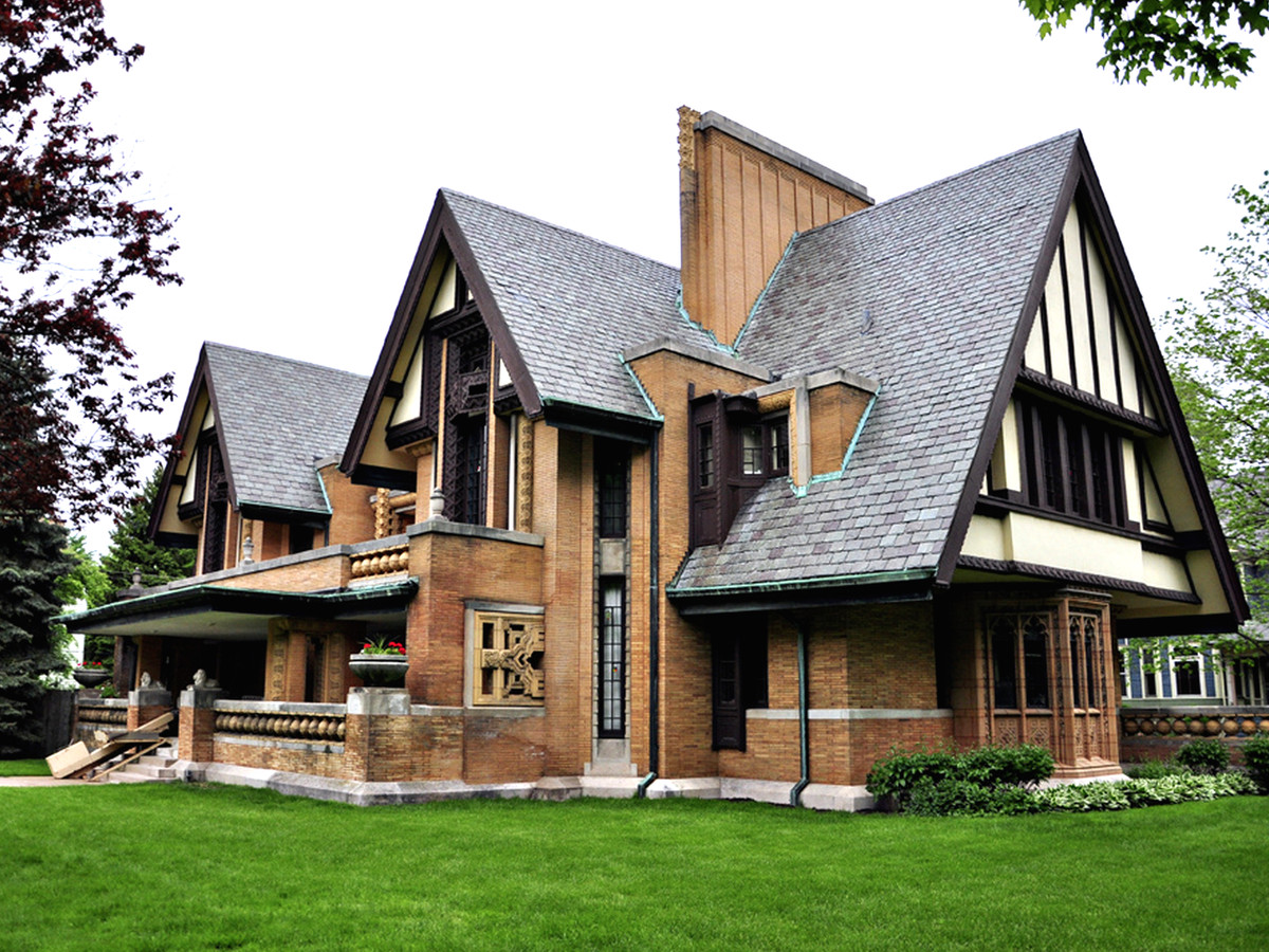 The exterior of a brown house with a black roof and Tudor design details.