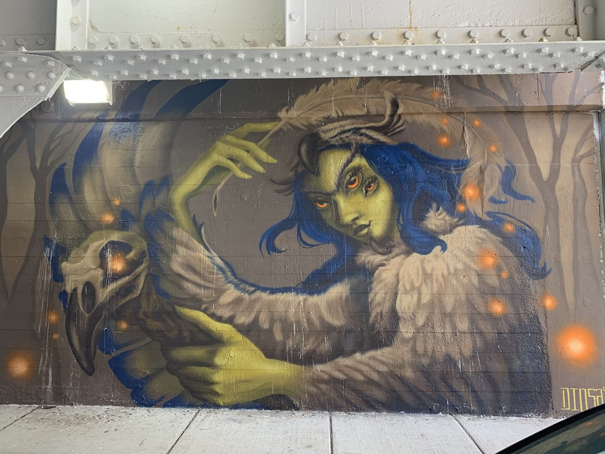 """This mural, by Little Village artist Jasmina Cazacu, focuses on """"La Chusa,"""" a """"vengeful spirit from Northern Mexican folklore,"""" according to Cazacu, whose professional name is """"Diosa."""" A woman """"was accused of witchcraft and unjustly murdered for it. Legend has it that, in the afterlife, she was enchanted with the form of an owl, so that she may roam the night and reveal herself as an omen of death to those reminiscent of her murders."""""""