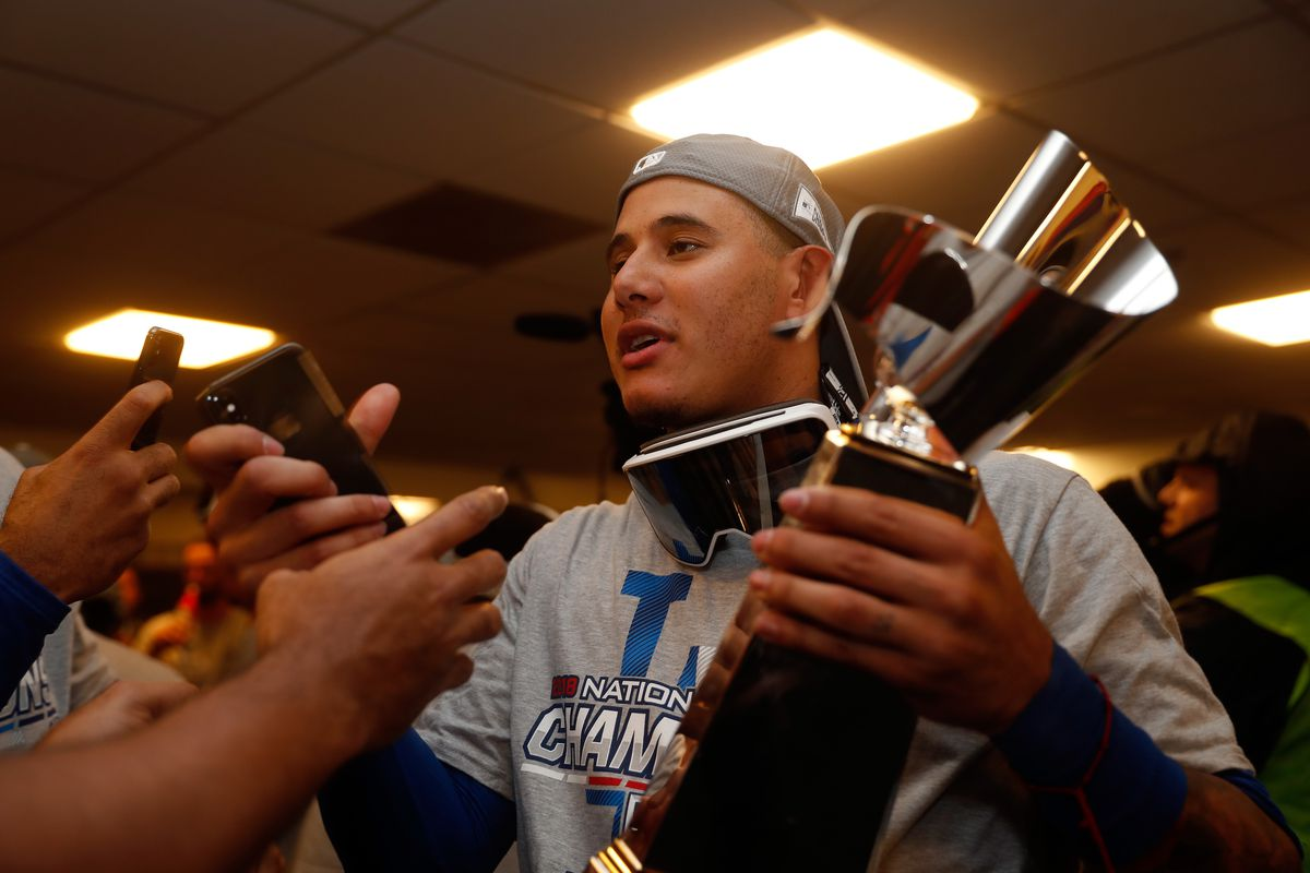 Manny Machado of the Los Angeles Dodgers celebrates with the Warren C. Giles Trophy in the locker room after defeating the Milwaukee Brewers in Game Seven to win the National League Championship Series at Miller Park on October 20, 2018.