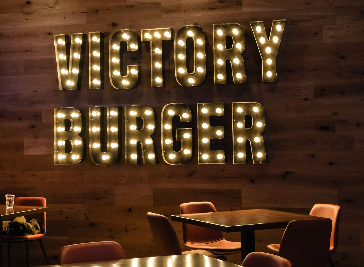 a lighted sign that spells Victory Burger