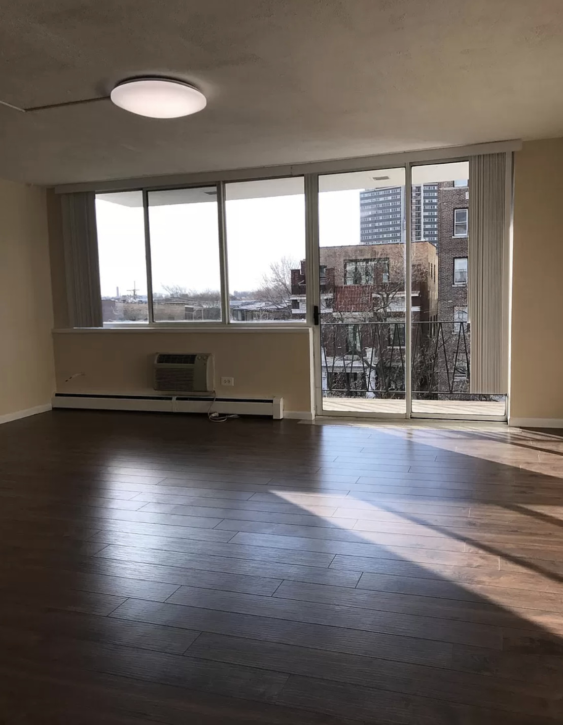 A room with a small balcony, hardwood floors, and a sliding glass door. There is natural light and a kitchen out of frame.