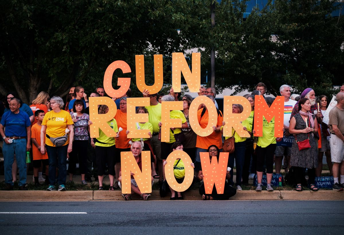 """Alt: Gun control advocates protest outside the NRA headquarters in Virginia by holding letters that spell out """"Gun reform now."""""""