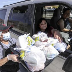 Nutrition technician Maria Orozco delivers a tray full of free meals to Sofia Faauila and Rosaline Latu outside of Edison Elementary School in Salt Lake City on Monday, Sept. 28, 2020. Nutrition technicians and kitchen managers typically hand out between 300 to 400 lunches a day at Edison. Meal service hours have extended and will now go from 10:30 a.m. to 12:30 p.m.
