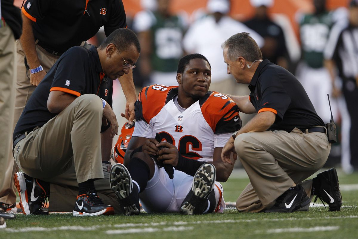 Aug 10, 2012; Cincinnati, OH, USA; Cincinnati Bengals defensive end Carlos Dunlap (96) is tended to by trainers during the game against the New York Jets at Paul Brown Stadium.  Mandatory Credit: Frank Victores-US PRESSWIRE