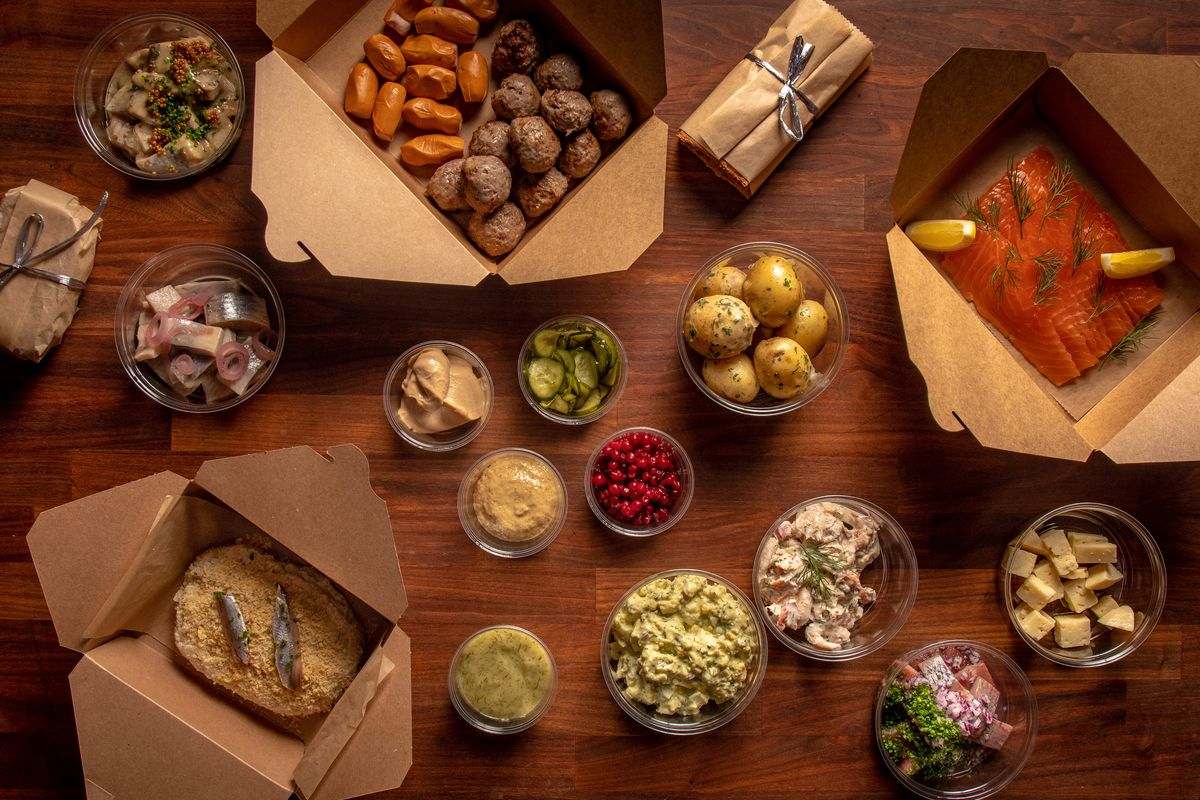 The Smorgasbord in takeout containers on a wooden surface